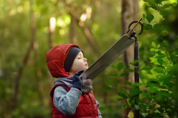 De kleine jongen leest een verklarend teken in de dierentuin of het park van aard.