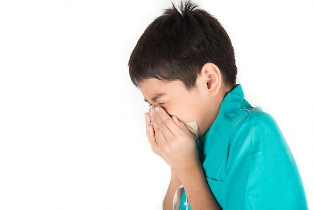 De kleine jongen niest en hoest van de griep met behulp van het schone weefsel