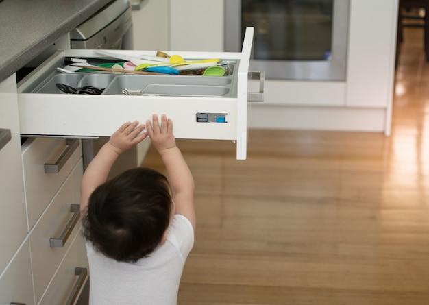 De kleine jongen opent de keukenladen om binnen met keukengereedschap te spelen