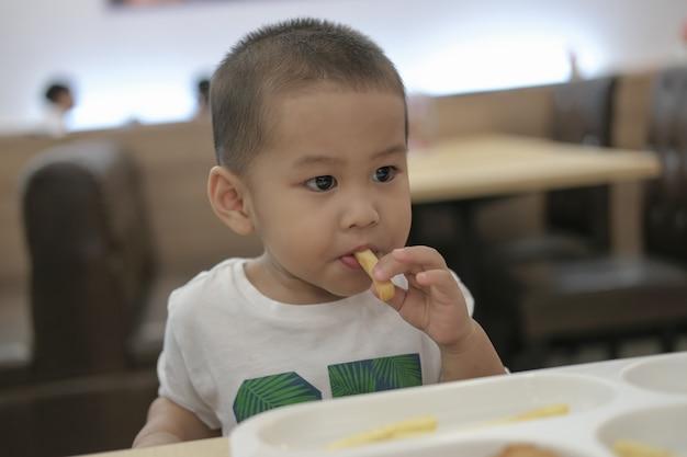 De kleine jongen was gelukkig aan het lunchen. gelukkig een familietijd.