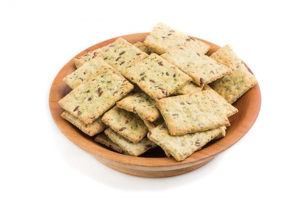 De kleine koekjes van broodspaanders met zaden in een houten die kom op wit wordt geïsoleerd. zijaanzicht