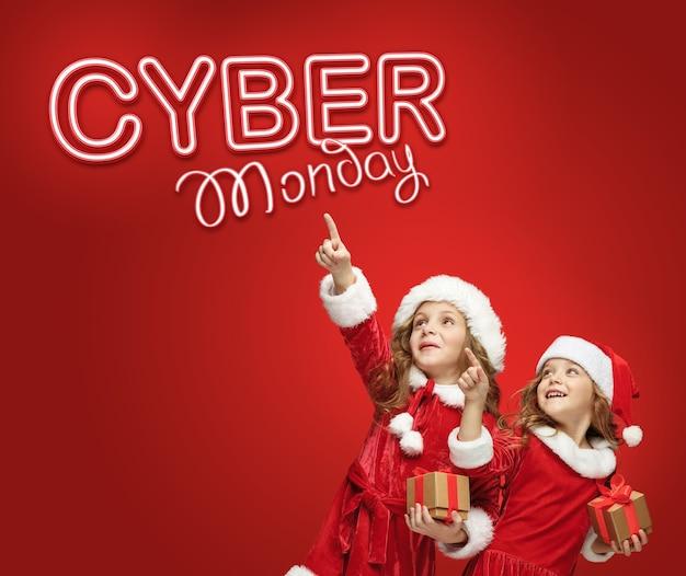 De kleine meisjes in kerstmuts met cadeautjes