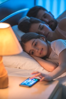 De kleine meisjestelefoon dichtbij de ouders in het bed. nachttijd