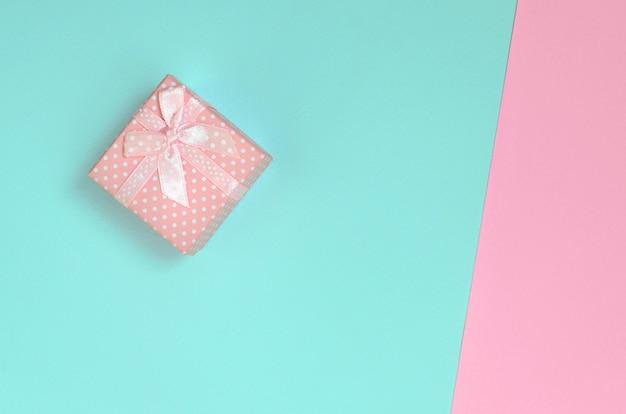De kleine roze giftdoos ligt op textuurachtergrond van blauw en roze manierpastelkleur