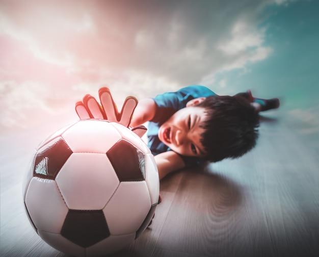 De kleine voetbalkeeper vangt voetbal met de achtergrond van de wolkenhemel.
