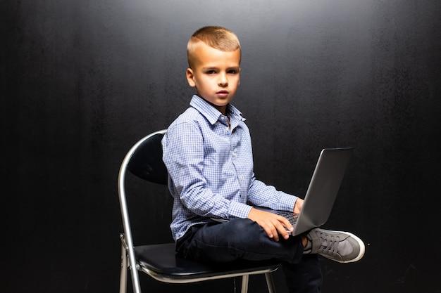 De kleine zitting van de schooljongen op stoel en laptop die op witte muur wordt geïsoleerd