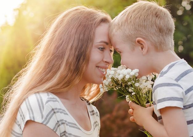 De kleine zoon geeft zijn moeder een boeket van delicate bloemen.