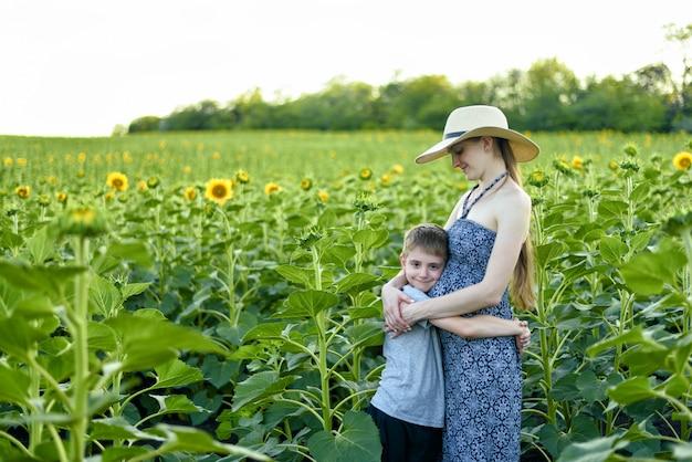 De kleine zoon omhelst zwangere moeder die zich op een gebied van bloeiende zonnebloemen bevindt
