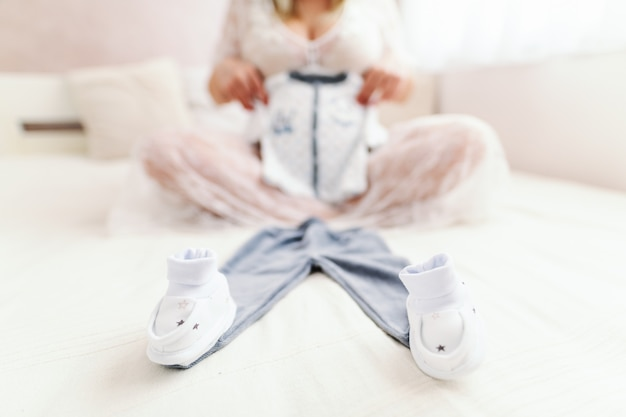 De kleren van de baby van de zwangere kaukasische vrouwenholding zullen zittend op het bed met benen in slaapkamer worden gekruist. selectieve focustechniek.