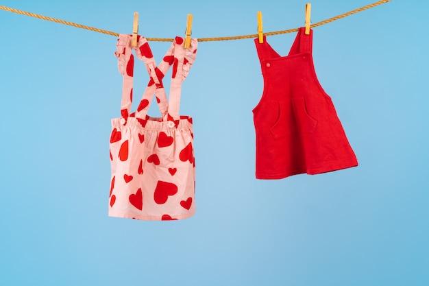 De kleren van het babymeisje op een drooglijn tegen blauwe achtergrond worden gespeld die