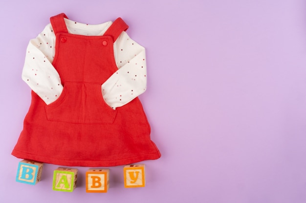 De kleren van het babymeisje op lila pastelkleuroppervlak