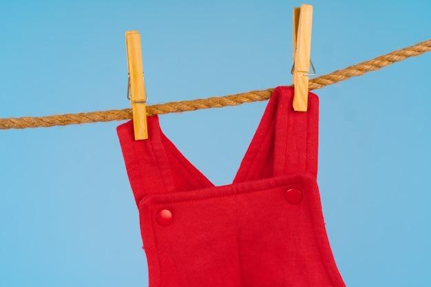 De kleren van het babymeisje vastgemaakt op een waslijn tegen blauwe achtergrond