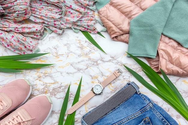 De kleren van maniervrouwen, tropische bladeren, trendy die toebehoren op marmeren achtergrond worden geplaatst.