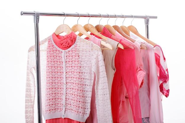 De kleren van roze vrouwen op houten hangers op rek op witte achtergrond. kast vrouwen jurken, blouses