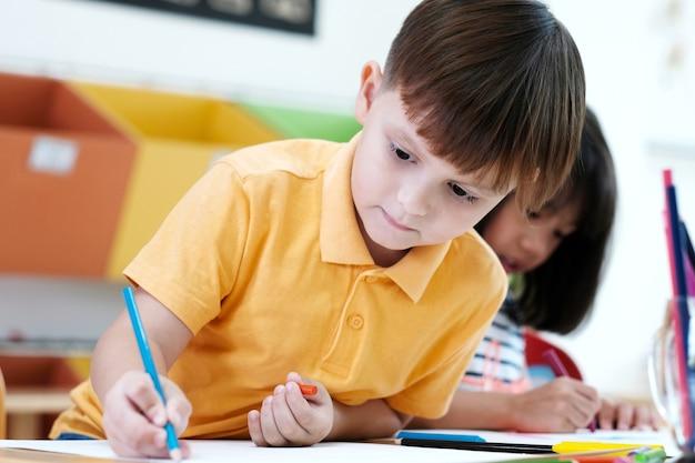 De kleurenpotloden van de jongenstekening in van het kleuterschoolklaslokaal, kleuterschool en jong geitje onderwijsconcept