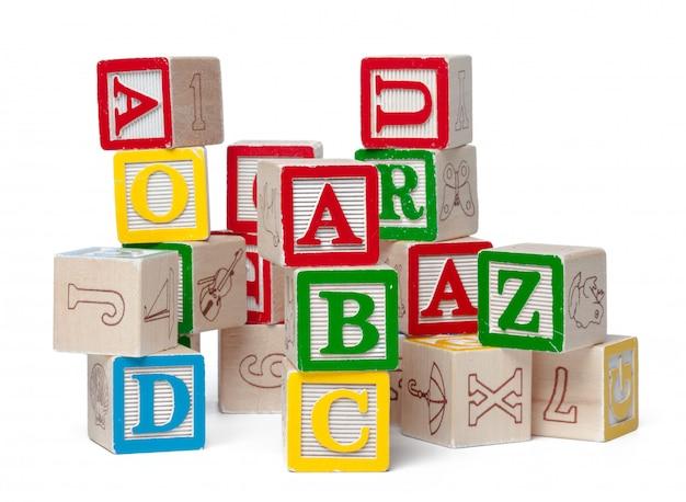 De kleurrijke alfabetblokken die worden gestapeld in knoeien geïsoleerd op wit