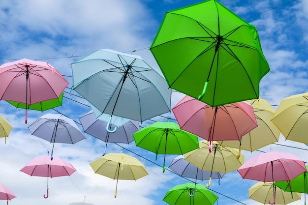 De kleurrijke buitensporige paraplulijn verfraait het openlucht bewegen door wind op blauwe hemel witte wolk