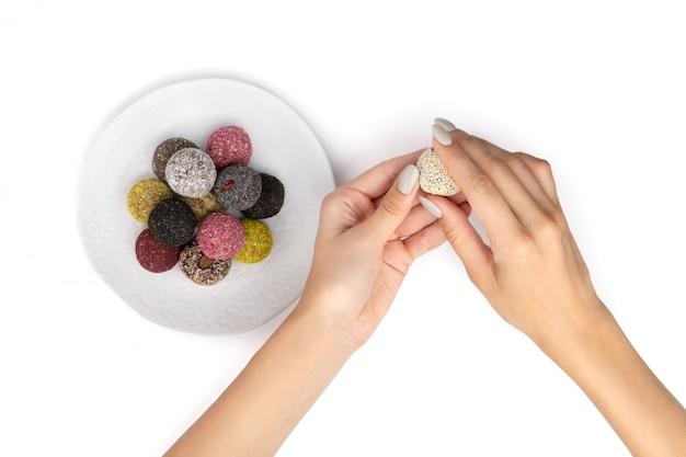 De kleurrijke de energieballen van het veganissuikergoed op plaat met de handen van de vrouw isoleerden wit