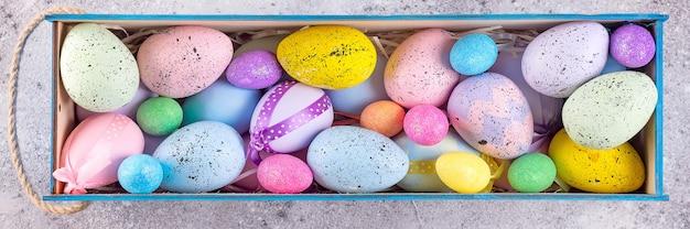 De kleurrijke die eieren van pasen in heldere kleuren met stronest in houten doos worden geschilderd