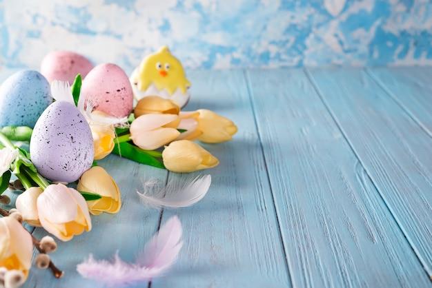 De kleurrijke eieren van pasen met tulpen op houten achtergrond als kader