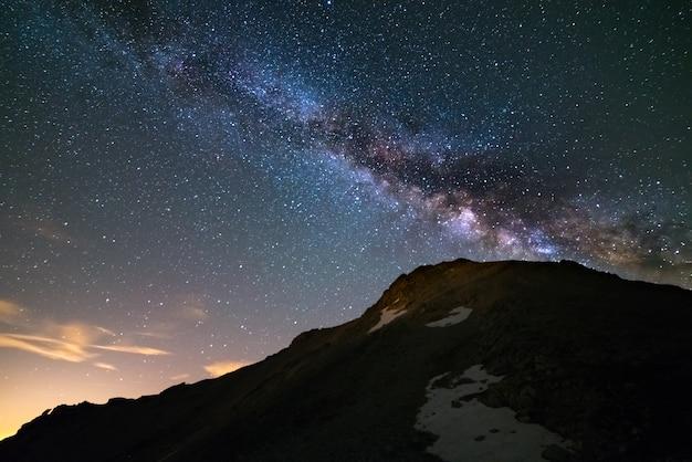 De kleurrijke gloeiende kern van de melkweg en de sterrenhemel gevangen op grote hoogte in de zomer op de italiaanse alpen, de provincie turijn.