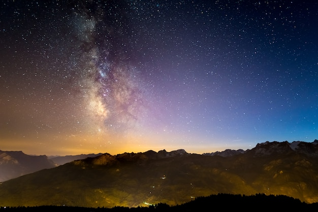 De kleurrijke gloeiende melkweg en de sterrenhemel boven de franse alpen en het majestueuze massif des ecrins.