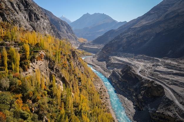 De kleurrijke herfst in hunza-vallei toont blauwe rivier en karakoram-bergketen.