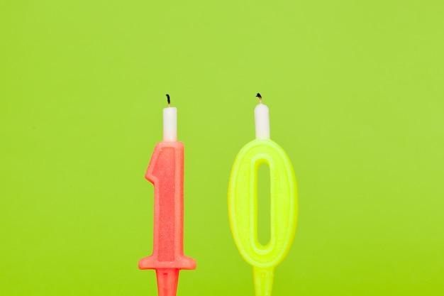 De kleurrijke kaars van de wasverjaardag op groen
