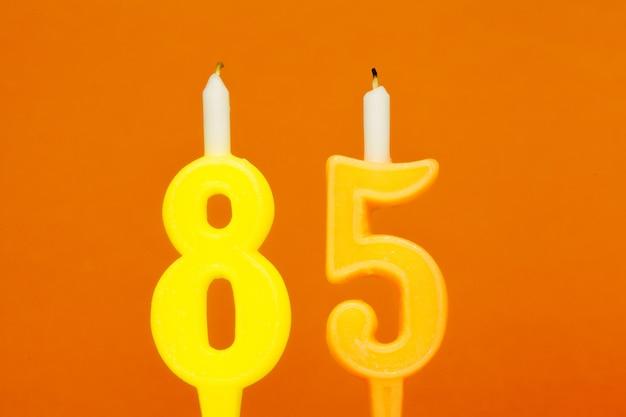 De kleurrijke kaars van de wasverjaardag op oranje achtergrond