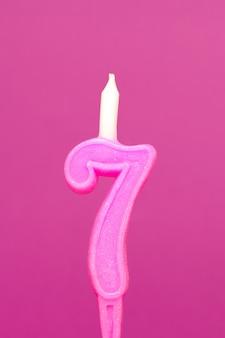 De kleurrijke kaars van de wasverjaardag op roze achtergrond