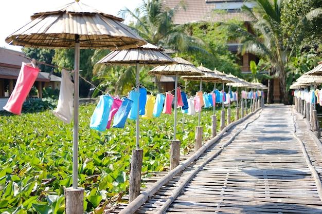 De kleurrijke lantaarn die van de stoffenlamp langs de houten voetgangersbrug van de bamboebrug in festival verfraaien