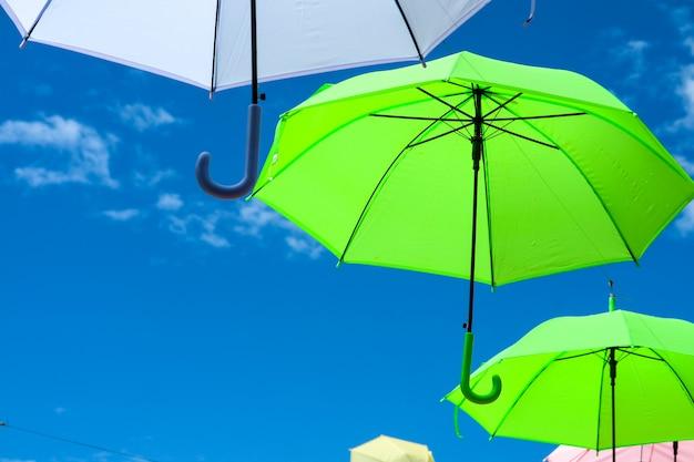 De kleurrijke paraplulijn verfraait het openlucht bewegen door wind op blauwe hemel witte wolk