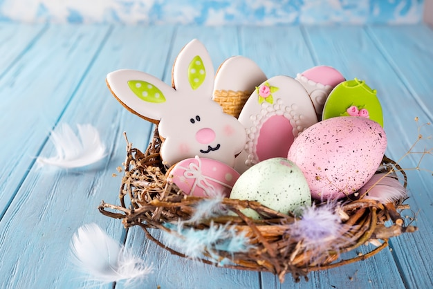 De kleurrijke pasen-koekjes van het eijpeind als konijn en ei in het nest op houten achtergrond