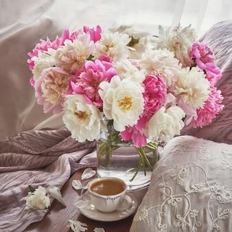 De kleurrijke pioen bloeit boeket in glasvaas, kop van koffie. afgezwakt beeld