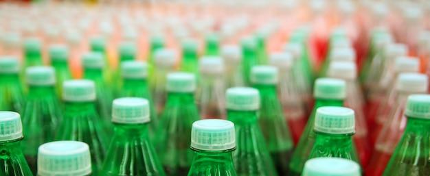 De kleurrijke plastic fles van de sapdrank in fabriek Premium Foto