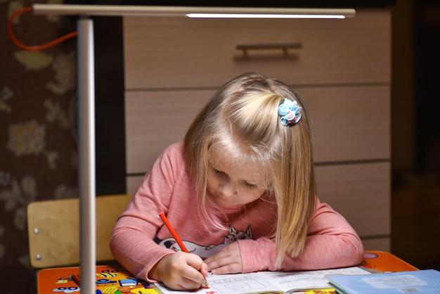 De kleuter leert om in notitieboekjes thuis te trekken en te schrijven