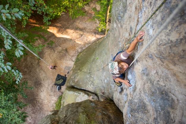 De klimmer van de vrouwenklimmer beklimt met karabijnen en kabel op een rotsachtige muur