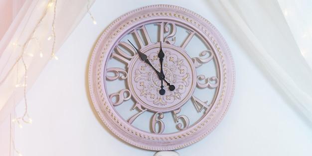 De klok aan de muur is roze. nog vijf minuten tot het nieuwe jaar. gelukkig nieuwjaar.
