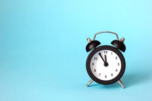 De klok is 23-55. zwarte wekker. het concept van het nieuwe jaar. de vakantie komt eraan.