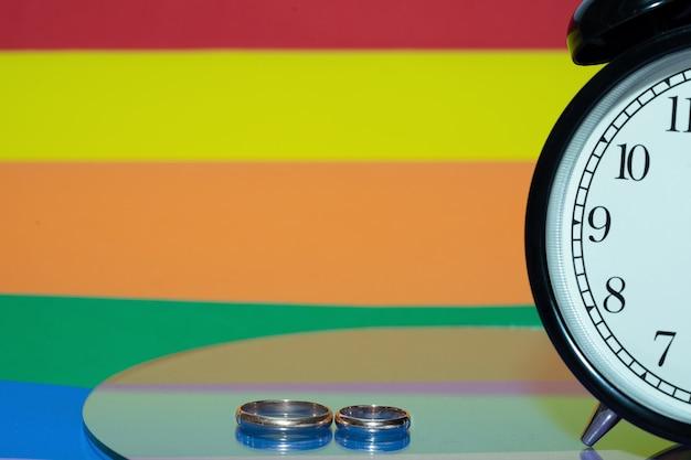 De klok op de achtergrond van de regenboogvlag, als symbool van