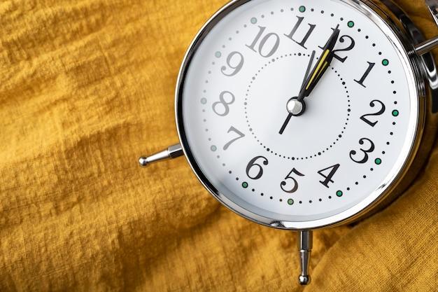 De klok plaats op de gele stof