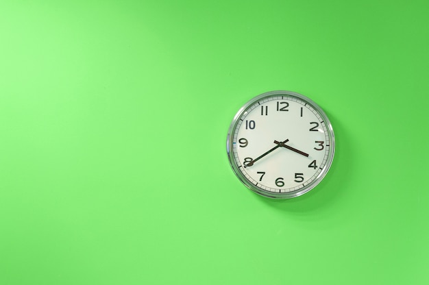 De klok van de close-upmuur die op groene achtergrond wordt geplaatst. het concept van de tijd is aan de gang. kopieer ruimte