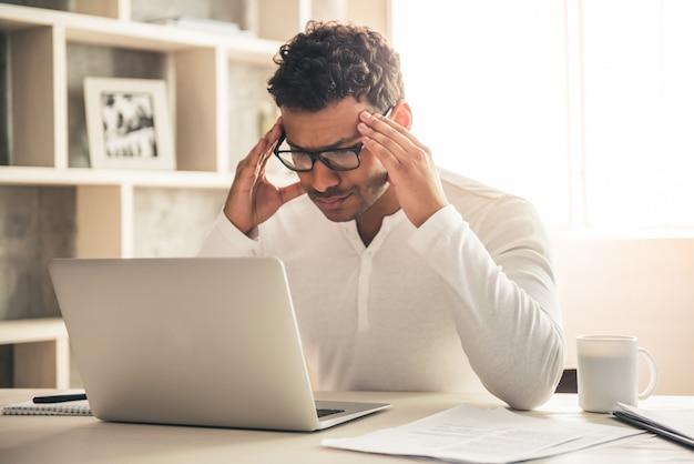 De knappe amerikaanse zakenman van afro gebruikt laptop.