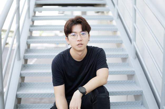 De knappe aziatische casual-glazenmens zit op een trap en glimlach het stellen