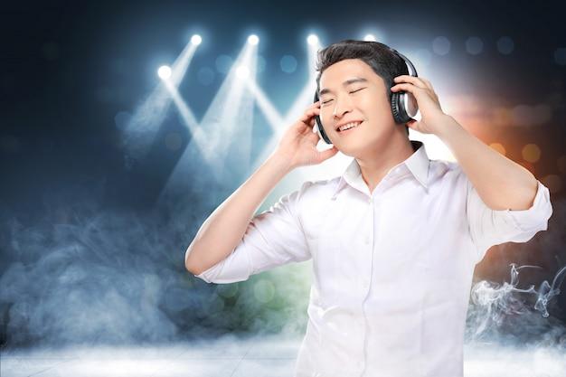 De knappe aziatische mens in wit overhemd met hoofdtelefoons geniet van de muziek
