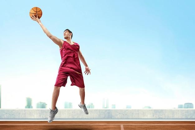 De knappe aziatische speler die van het mensenbasketbal hoog springen en de bal terugkaatsen om in openluchtbasketbalhof te scoren