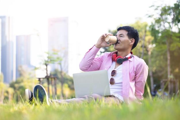 De knappe aziatische zakenman drinkt koffie en communiceert met zijn laptop op groen gras in een central park