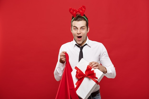 De knappe bedrijfsmens vier vrolijke kerstmis en gelukkige de rendierhaarband die van het jaarslijtage de rode grote zak van de kerstman houden.