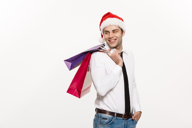 De knappe bedrijfsmens viert vrolijk kerstfeest met kerstmuts met boodschappentas.