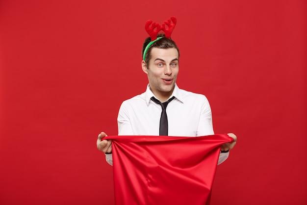 De knappe bedrijfsmens viert vrolijke kerstmis die rendierhaarband draagt die kerstman rode grote zak houdt.